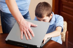 Photo of adult closing a computer and child bending down to see screen, limit screen time in children