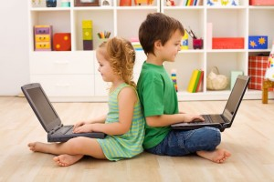 Photo of two children sitting back to back each with a laptop computer children spen 7 hours per day in front of digital screens