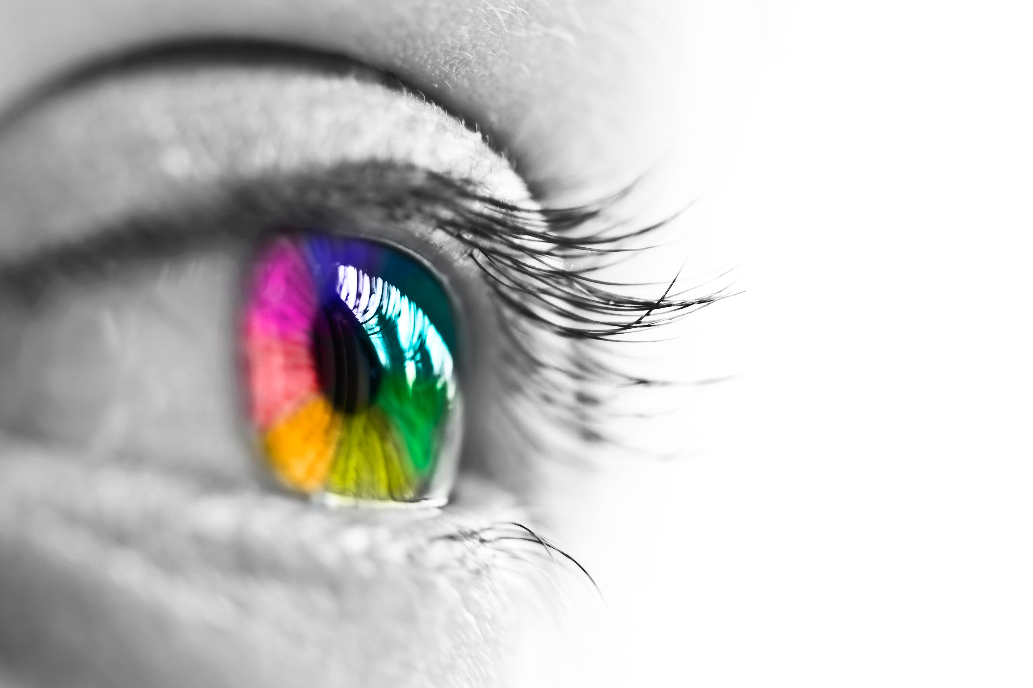 A black and white picture of an eye with a bright rainbow colored iris.