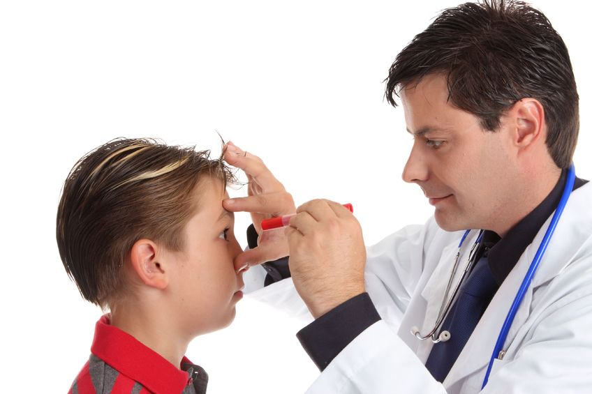 A young boy having his eyes check for responsiveness by a doctor with a flashlight for visual perceptual motor deficit